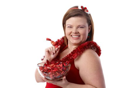 Plump woman in red with a bowl of Christmas fondant, smiling. photo
