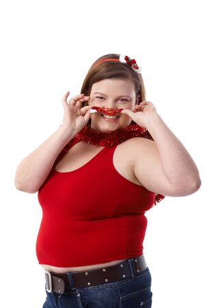 Fat woman in red forming moustache of christmas fondant, having fun, smiling. photo