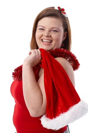 Happy plump woman holding santa hat, smiling, looking at camera. photo