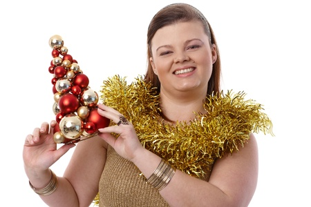Christmas portrait of happy plump woman holding small christmas tree, smiling. Stock Photo - 14426794