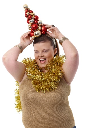 Overweight young woman holding a small christmas tree on head, smiling happily. photo