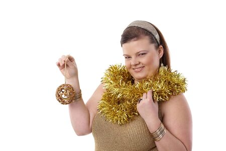 Christmas portrait of overweight woman holding christmas ornaments, smiling. photo