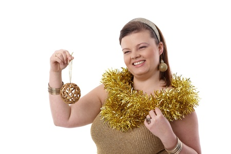 Happy plump woman holding christmas ornaments in hand, smiling. photo