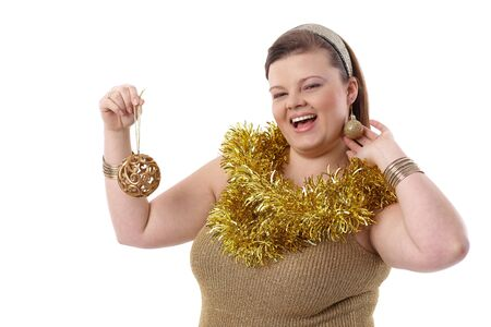 Overweight young woman smiling, holding christmas ornaments in hand. photo