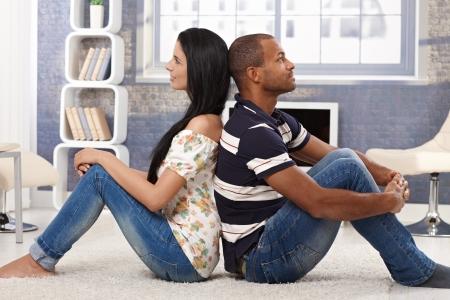 Heureux couple interracial assis sur le plancher arrière-to-back, la rêverie, en souriant.