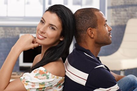 Happy interracial loving couple sitting at home back-to-back, smiling. photo