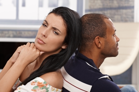 Young woman and man sitting back-to-back unhappy. Stock Photo - 14426856