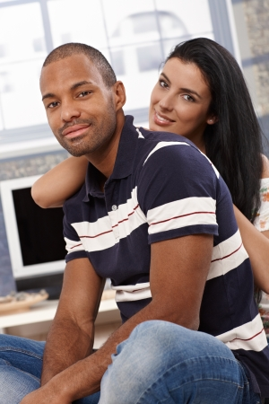 Attractive young interracial couple sitting, embracing at home, smiling. photo