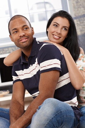 Portrait of beautiful young diverse couple at home, smiling, embracing. photo