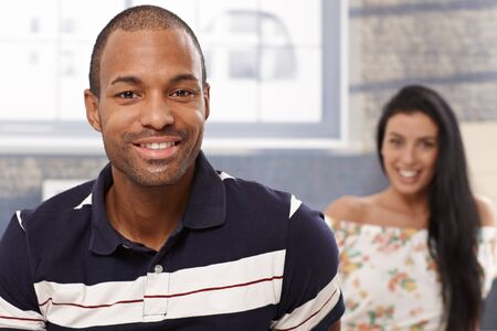 stockphoto: Portrait of handsome black man smiling, girlfriend at the background.