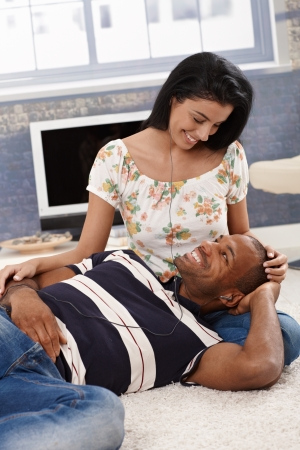 Loving interracial couple listening to music through earbuds at home, smiling at each other. Stock Photo - 14426875