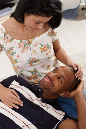 Diverse couple listening to music at home, man lying in womans lap, both smiling. photo