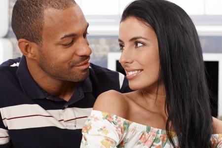 pareja hogar: Amando pareja mixta mirando el uno al otro, justo a punto de besarse con una sonrisa.