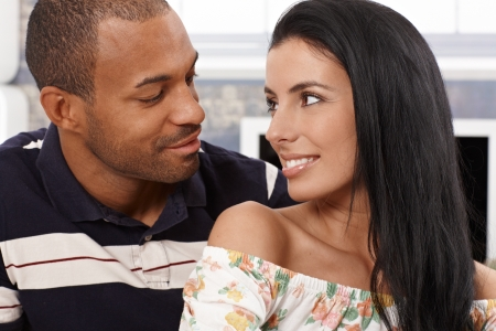 mixed races: Loving mixed race couple looking at each other just about to kiss, smiling. Stock Photo