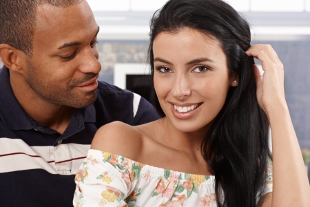 interracial relationships: Portrait of attractive young interracial couple at home, smiling.
