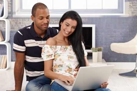 Young attractive diverse couple browsing internet, using laptop computer, smiling. photo