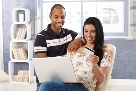 Diverse couple e-shopping at home, using credit card, smiling. photo