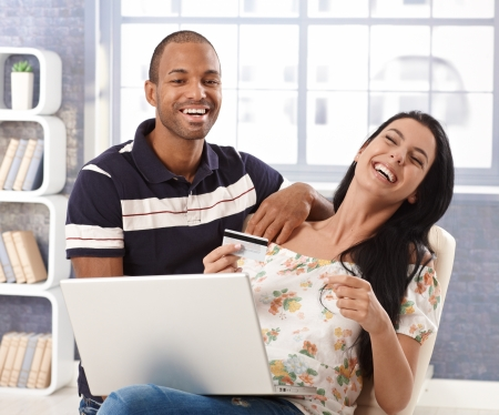 Happy interracial couple shopping online at home, using credit card, laughing. photo