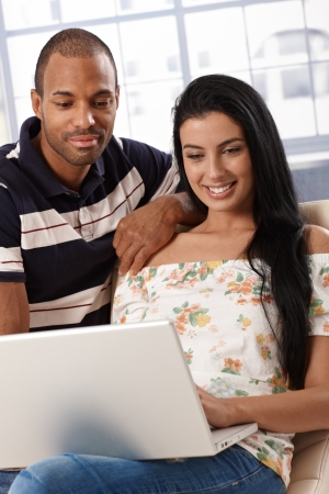 Attractive young mixed race couple browsing internet at home on laptop computer, smiling. photo