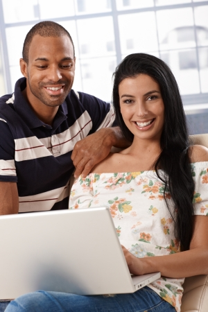 Happy diverse couple using laptop computer at home, smiling. photo