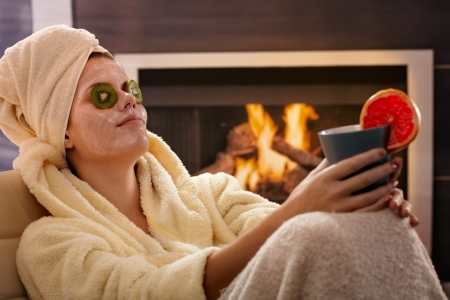 resting mask: Woman in bathrobe and towel relaxing in facial mask, fruit pack, holding tea mug in front of fireplace. Stock Photo