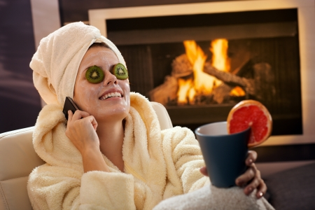 Happy woman in facial pack smiling, talking on mobile phone, holding tea mug, wearing bathrobe and towel by fireplace. photo