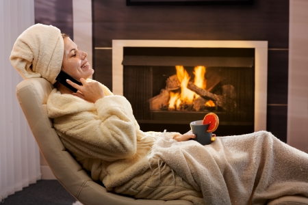 Happy woman relaxing in beauty mask, wearing bathrobe, talking on mobile phone, sitting in cosy living room armchair, in front of fireplace. photo
