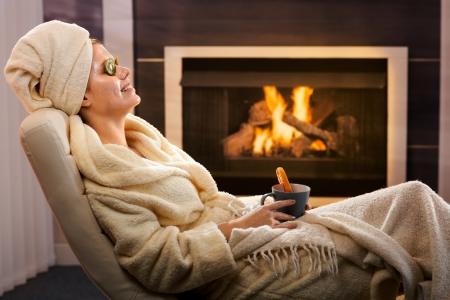 Young woman in cosy living room enjoying winter relaxation with face pack and tea, smiling. photo