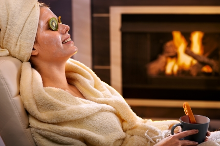 tea cosy: Smiling woman relaxing at home with kiwifruit facial mask and tea mug, sitting in bathrobe in front of fireplace.