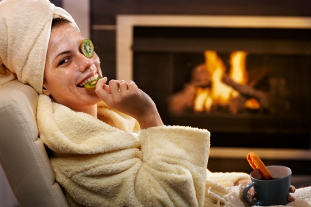 Funny woman eating fruit from kiwi facial mask, smiling, sitting in bathrobe in front of fireplace. photo