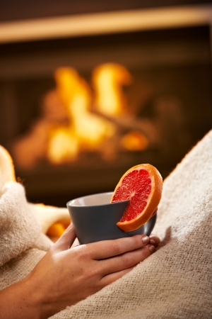 Having hot tea with blood orange in front of fireplace, female hand holding mug. photo