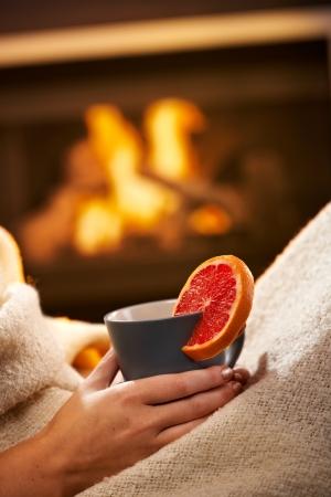red bathrobe: Having hot tea with blood orange in front of fireplace, female hand holding mug. Stock Photo