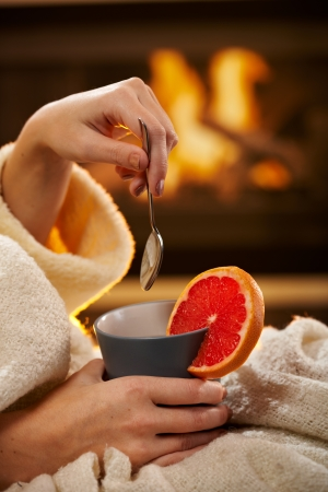 Winter evening with hot blood orange tea, young woman in bathrobe holding mug and spoon in front of fireplace.
