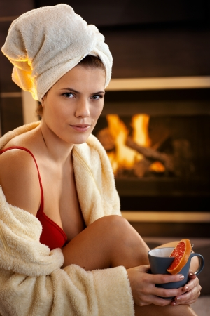 Hot young woman smiling, having tea in bathrobe and red bra in front of cosy fireplace. photo