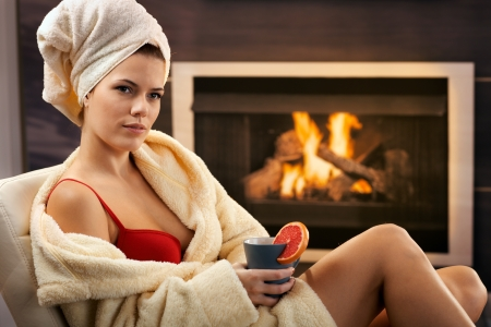 Pretty woman relaxing in bra and bathrobe, enjoying hot tea in front of fireplace. photo