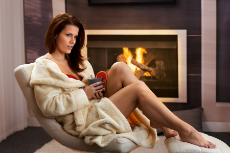 Winter portrait, sexy young woman in cosy bathrobe having tea with blood orange at home, sitting in front of fireplace, daydreaming. photo