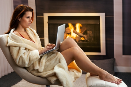 woman bathrobe: Hot woman sitting in bathrobe using laptop computer in front of fireplace, enjoying winter leisure. Stock Photo