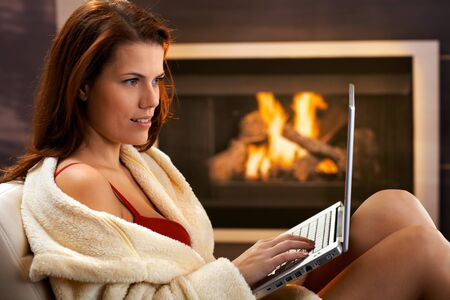 Winter portrait of young woman using laptop computer in bathrobe and red bra in front of fireplace, smiling. Stock Photo