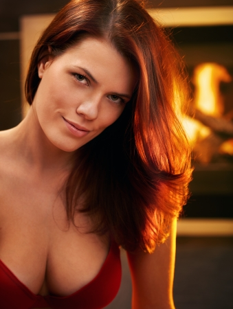 20s  closeup: Portrait of sexy young woman in red bra smiling in front of fireplace.
