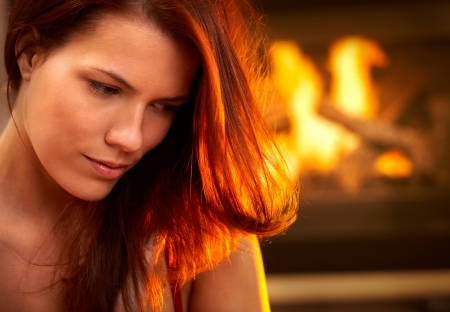 Portrait of attractive woman looking down, daydreaming in front of fireplace. Stock Photo