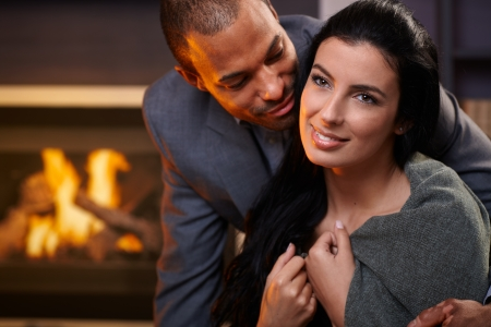 Attractive interracial couple embracing at home by fireplace. photo