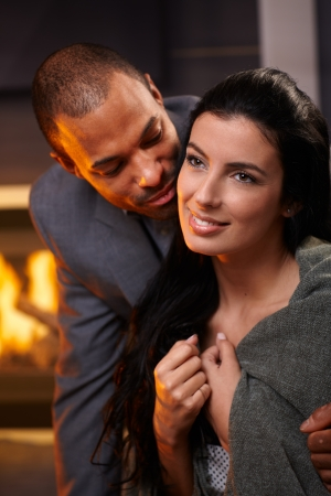 Beautiful diverse couple embracing at home by fireplace, smiling. photo