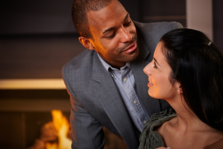 be kissed: Portrait of happy loving mixed race couple at home. Stock Photo