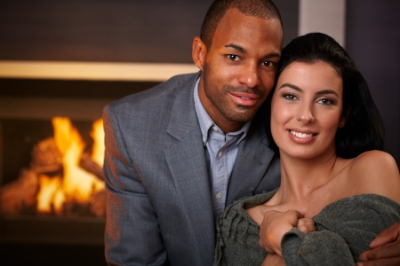 Portrait of beautiful young interracial couple, smiling at home by fireplace. photo