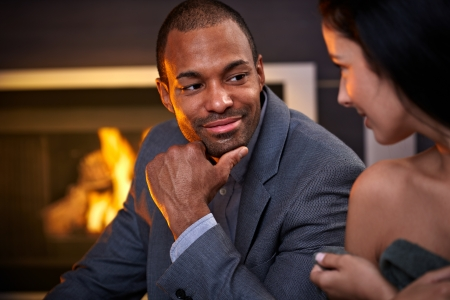 Young attractive multiethnic couple sitting by fireplace at home, talking, smiling. photo
