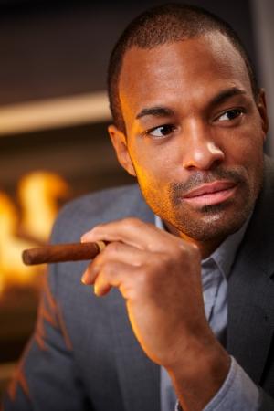 Close-up portrait of elegant black man smoking cigar by fireplace. photo