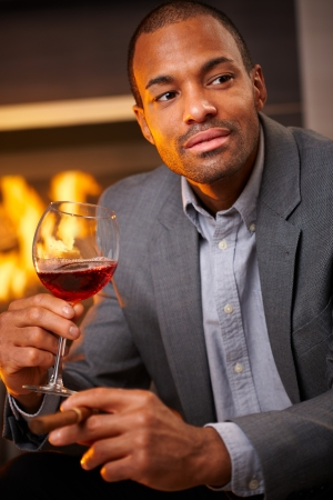 Handsome black man sitting by fireplace smoking cigar, drinking wine. photo