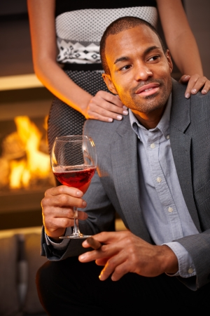 Goodlooking ethnic man sitting by fireplace smoking cigar, drinking wine, girlfriend standing behind. photo
