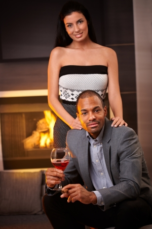 Portrait of attractive interracial couple at home by fireplace. photo
