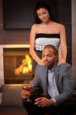 Elegant mixed race couple at home by fireplace, man holding glass of wine and cigar. photo